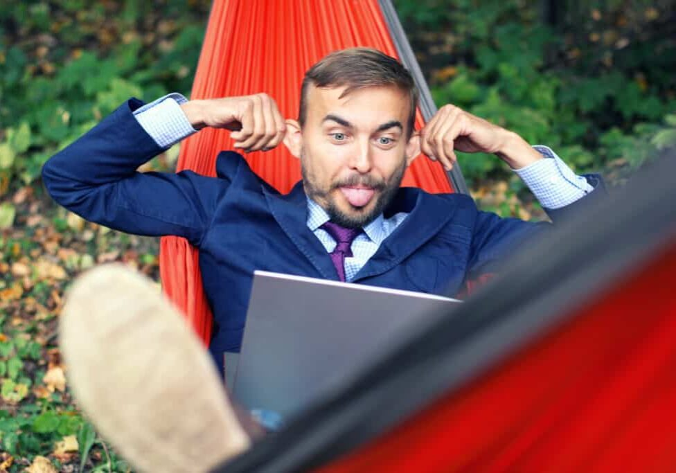 Businessman with laptop relaxs in a hammock on nature. He talking on video chat and doing funny faces with his tongue hanging out and splayed ears. Freelance or telework, on-line chatting concept.